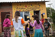A group of children trying out their stilts outside the community library, Biblioteca Comunitaria do Arquipelago, Porte Alegre, Brazil. <br /> <br /> Once a week the children have a music and poetry session where they go out in to the community on stilts singing, playing music and reciting poetry.<br /> <br /> Cirandar is working in partnership with  C&A and C&A Instituto to implement a network of Community Libraries in eight communities of Porto Alegre.
