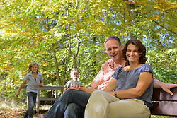 Father and mother sitting on bench while their children run around, Bavaria, Germany