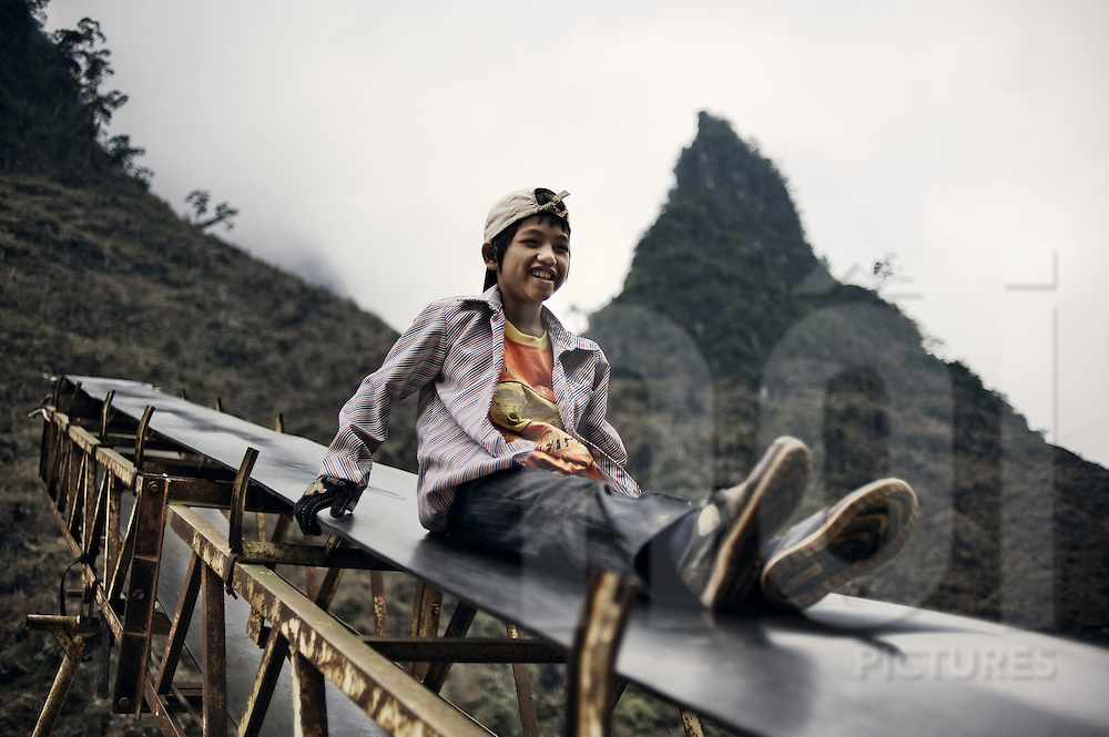 A boy laughs as he slides down a conveyor belt in the mountains of Ha Giang Province, Vietnam, Southeast Asia