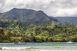 Moored boats on Hanalei Bay on the North shore of Kauai, Hawaii,  Mamalahoa Mountain towering above.