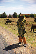 Captioned as 'Basuto herdsman with traditional blanket' standing near his cattle, South Africa 1979