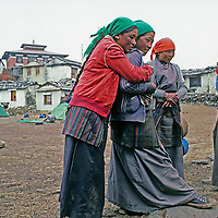 Young Sherpa [Sherpani] women at Nepal's old Tengboche Monastery watch as young monks play (out of frame.)