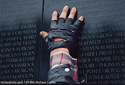 iTouch the Wall. Washington DC., Memorial Day, 1995<br /> <br /> Limited Edition Print from an edition of 50. Photo ©1995 Michael Lichter.<br /> <br /> The Story: Spirits run high in the Pentagon parking lot on Memorial Day. Tens of thousands of motorcycles parade through the streets of DC, spectators cheering the entire way. By the time we arrived at the wall, the mood, magnified by the rain, had become somber. You could see it in the way people walked, the way they talked, in their faces and in their every gesture.