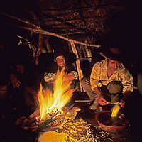 Peruvian arrieros (mule drivers) laugh around a campfire as they camp on the trail while working with a National Geographic archaeology expedition to the Cordillera Vilcabamba mountains in the Andes.  One is skinning a trout he had just caught in a stream.