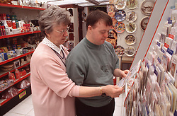 Mother and adult son with Downs Syndrome looking at greeting cards in shop,
