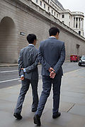 Two businessmen walk along a street, both with hands clasped behind their backs, in the City of London - the capitals financial district, on 4th June 2018, in London, England.