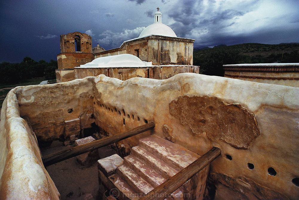 Afternoon lightning and thunderstorm approach the ruins and the restored church. Tumacacori Mission. Tucson, Arizona, USA.