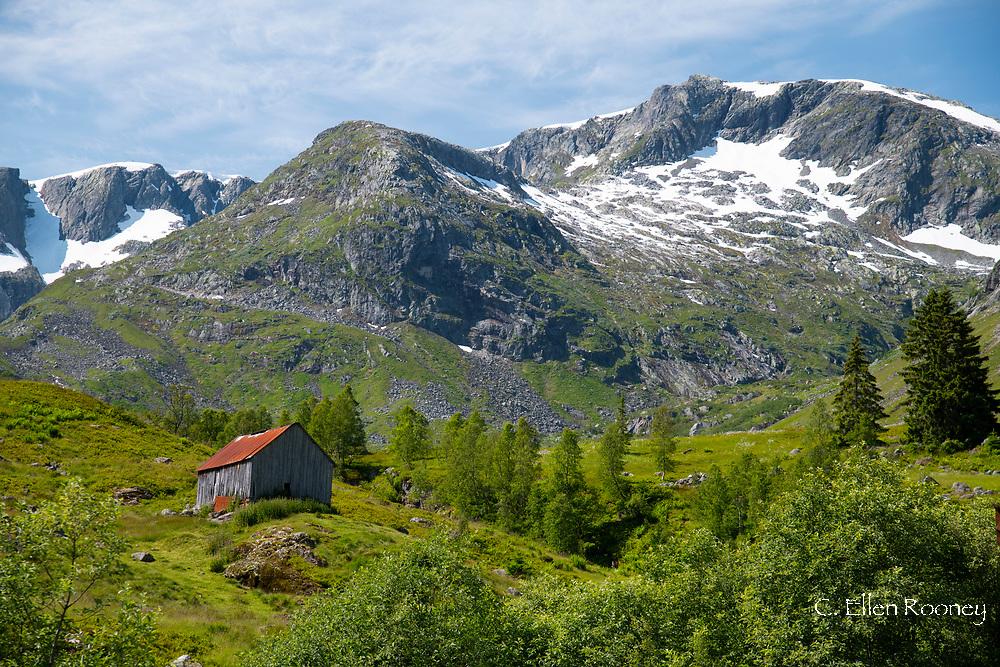 A wooden barn on a hillside below the Frudalsbreen Glacier, Vestlandet, Norway