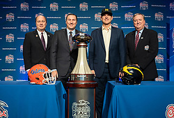(L-R) Peach Bowl, Inc. president and CEO Gary Stokan and Peach Bowl, Inc. chairman Bob Somers appear with Florida Gators head coach Dan Mullen and Michigan Wolverines head coach Jim Harbaugh as they pose for a photo with the 2018 Chick-fil-A Peach Bowl trophy at the coaches news conference on Friday, December 28, 2018 in Atlanta. Florida and Michigan face off in the Peach Bowl NCAA football game on December 29, 2018. (Paul Abell via Abell Images for the Chick-fil-A Peach Bowl)