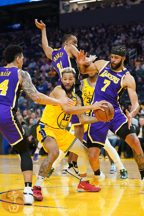 February 27, 2020; San Francisco, California, USA; Golden State Warriors guard Ky Bowman (12) is defended by Los Angeles Lakers guard Danny Green (14), guard Avery Bradley (11) and center JaVale McGee (7) during the third quarter at Chase Center.