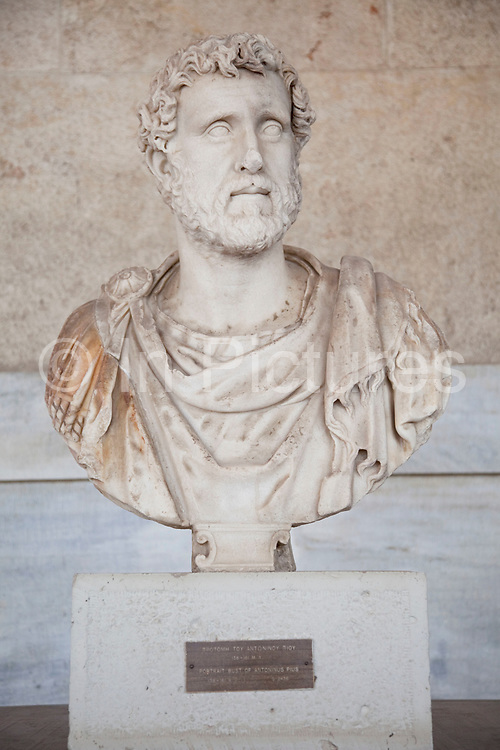 Portrait bust of Antoninus Pius at The Stoa of Attalos or Attalus located in the east side of archaeological site of the Ancient Agora in Athens just oposite the Adrianou street in Monastiraki. The Stoa of Attalos was built around 150 BC, by Attalos II, King of Pergamos as a donation to Athens. The construction of the building began in 159 BC and ended in 138 BC. The building was the largest in length in Greece during the antiquity. It was rebuilt in the same style and shape from 1953 to 1956 with beautifully crafted marble columns. It is recognised as one of the most impressive stoa in the Athenian Agora. Typical of the Hellenistic age, the stoa was more elaborate and larger than the earlier buildings of ancient Athens. The stoa's dimensions are 115 by 20 metres wide (377 by 65 feet wide) and it is made of Pentelic marble and limestone. The building skillfully makes use of different architectural orders. The Doric order was used for the exterior colonnade on the ground floor with Ionic for the interior colonnade. Athens is the capital and largest city of Greece. It dominates the Attica periphery and is one of the world's oldest cities, as its recorded history spans around 3,400 years. Classical Athens was a powerful city-state. A centre for the arts, learning and philosophy.