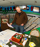 """Bill Colby pulls out the 1971 season his group is currently playing with the Strat-O-Matic game in his """"Fenway Park"""" room.  (Karen Bobotas/for the Laconia Daily Sun)"""