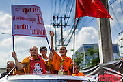 08 MAY 2013 - BANGKOK, THAILAND:  Buddhist monks wave to the crowd during a motorcade to the Thai parliament building. A splinter group of the Red Shirts, Thai supporters of exiled Prime Minister Thaksin Shinawatra, have besieged the Thai Constitutional Court for the last three weeks calling for the resignation of the justices, who have indicated they might oppose a proposed constitutional reform which would grant amnesty to people convicted of political crimes since 2007. This would probably include Thaksin. The justices have refused to step down. Wednesday the protesters moved their protest to the Thai Parliament, which is largely powerless to intervene.  PHOTO BY JACK KURTZ