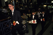 Young Hungarians wearing formal suits with bow ties carry their McDonalds meals soon after it opened in central Budapest, the first in Hungary, on 18th June 1990, in Budapest, Hungary.