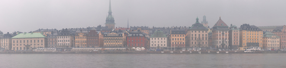 The water front at Gamla Stan, The Old Town, Skeppsbron, in foggy winter weather, with 16th and 17th century buildings. Stockholm. Sweden, Europe.