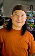 Hmong cook at concession stand taking a moment for a portrait. Hmong Sports Festival McMurray Field St Paul Minnesota USA