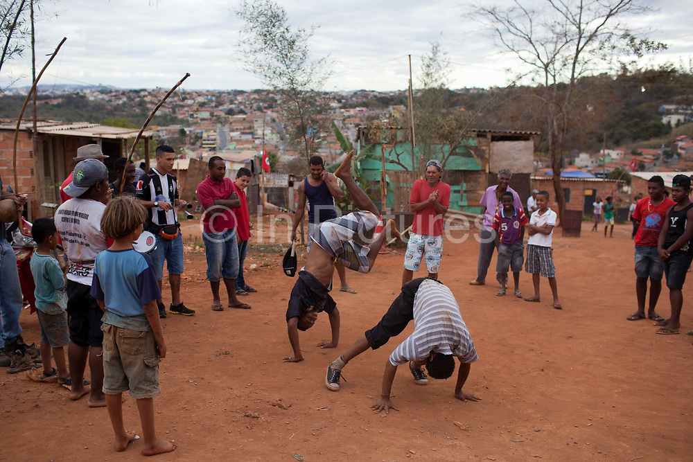 Men practicing Capoeira on the dirt road. Isidoro occupation in Belo Horizonte, Minas Gerais in a large  amount of land that was occupied by the MLB, a Brazilian workers social movement, it faced eviction in July / August 2014. (photo by Phil Clarke Hill/In Pictures via Getty Images)