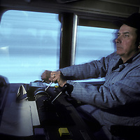 Canada, Ontario, (MR) Engineer Mel Wartig at controls of VIA Rail train locomotive in eastern Ontario