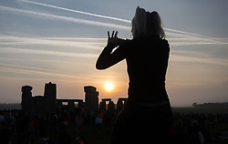 People watch the sunrise at Stonehenge in Wiltshire on the Summer Solstice.