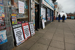 © Licensed to London News Pictures. 25/03/2016. <br /> <br /> Pictured: A shop keeper looks out of his shop which displays a headline regarding the murder located next to the crime scene - Delicious Deli near Fleming Street, Clydebank.<br /> <br /> Police Scotland have focused the centre of the murder investigation of 15 year old Paige Doherty in Clydebank, Glasgow around the home and business premises of suspect John Leathem as they search his house and Delicious Deli near Fleming Street, Clydebank Glasgow on Friday 25th March 2016.<br /> <br />  Photo credit should read Max Bryan/LNP