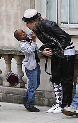 ©London News Pictures. 15/01/2011 .Picture Credit Should read Neil Hall/London News Pictures.Madonna directs her new period film W.E. starring Abbie Cornish about the abdication of King Edward in London on 08/08/2010 Pictured is Madonna kissing her adopted son David and causing his hat to fall off