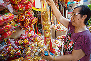 """22 JANUARY 2013 - BANGKOK, THAILAND:   A customer looks at Chinese New Year merchandise on display in a shop on Charoen Krung Road in Bangkok's Chinatown district. Chinese New Year is not an official public holiday in Thailand, but it is one the biggest celebrations in the Bangkok, which has a large Chinese population. Chinese New Year is February 10 this year. It will be the """"Year of the Snake.""""    PHOTO BY JACK KURTZ"""