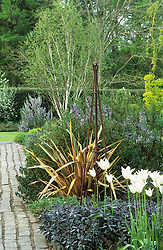 Rusty obelisk surrounded with bronze fennel, purple sage and Tulipa 'White Triumphator' . Brick path leading into the distance.