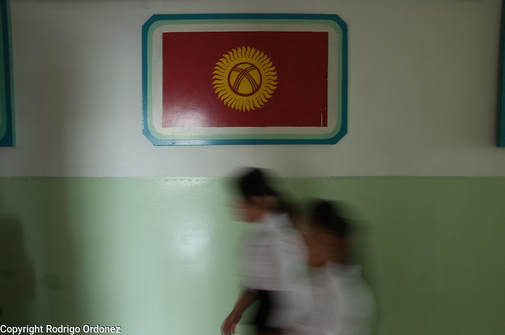 Girls in school uniform walk by a Kyrgyz national flag painted on the walls of Mombekova School (in Osh, Kyrgyzstan) during the ceremony to mark the 'first bell', or first day of school, on September 1, 2010.