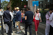Tour guide holds a blue folder aloft to make sure her tourist grop can follow, Kings Road, Chelsea, London, UK.