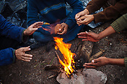 Central American migrants gather around a campfire to warm their hands while wait the departure time of the train to continue their journey to the north, in State of Mexico, Mexico, September 20, 2008.