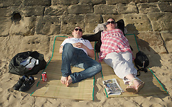 © Licensed to London News Pictures. 28/03/2012..Saltburn, England..As temperatures rise this week the beach at Saltburn in Cleveland attracts the visitors as they enjoy the warm weather. Scott and Leanne Pickering from Middlesbrough take it easy on the beach...Photo credit : Ian Forsyth/LNP