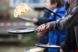 © Licensed to London News Pictures. 09/02/2016. Ilkley, UK. A competitor practices his pancake flip on the start line for this year's pancake race in Ilkley, West Yorkshire. The race is held annually in the Yorkshire town of Ilkley on Shrove Tuesday. Photo credit : Ian Hinchliffe/LNP