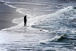 A woman seen in silhouette and at a distance standing alone on Fistral Beach in Newquay, Cornwall.
