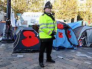 © Licensed to London News Pictures. 13/11/2011. London, UK. A police man next to tents decorated with red poppies. Occupy London protest camp During the Remembrance Service held at St Paul's Cathedral in London today, 13th November 2011. Photo credit : Stephen Simpson/LNP