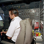 An airline flight-engineer occupies his own seat in the cockpit of a Boeing 747 - before the era arrived when technology made his role as a third flight crew member redundant. With a bowl of fresh fruit beside his seat, the male member of the flight-deck crew watches instruments and readings in front of the unseen pilots at the front. Wearing the three stripes designating his rank and seniority within his unspecified airline, the specialist's skills are in engineering systems that maintain efficient flight. When introduced, the Boeing 747-400 model was equipped with a two-crew glass cockpit, which dispensed with the need for a flight engineer - many of whom lost their jobs or retrained as pilots themselves.