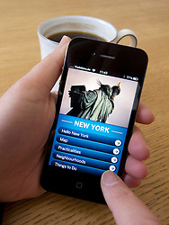 Reading travel guide to New York on an Apple iphone 4G smart phone