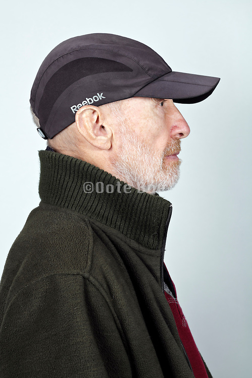 side view portrait 70 year of age person wearing a baseball cap