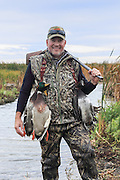Successful waterfowl hunter Mike Brandreit with the results of a morning shoot on the Delta Marsh in Manitoba.
