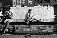 Old-fashioned paper and modern electronic readers at the fountain in Lincoln Center, New York City