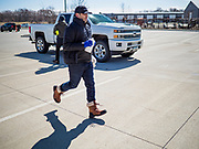 """20 MARCH 2020 - DES MOINES, IOWA: ANDREW TOMES, the brand manger at the Foundry, a distillery in Des Moines, runs through the parking lot while handing out hand sanitizer to waiting motorists. The distillery suspended its distilling operations to make hand sanitizer this week. They distributed it free to people who came to their building. On Friday thousands of people came to get some. There line was more than one mile long. On Friday morning, 20 March, Iowa reported 45 confirmed cases of the Coronavirus. Restaurants, bars, movie theaters, places that draw crowds are closed for at least 30 days. There are no """"shelter in place"""" orders in effect anywhere in Iowa but people are being encouraged to practice """"social distancing"""" and many businesses are requiring or encouraging employees to telecommute.  PHOTO BY JACK KURTZ"""