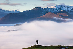© Licensed to London News Pictures. 07/12/2020. Keswick UK. A photographer stands at the top of Latrigg fell & watches the fog this morning that is covering the town of Keswick bellow as much of the UK has been affected by freezing fog today. Photo credit: Andrew McCaren/LNP