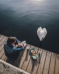 THEMENBILD - ein neugieriger Schwan neben einem Steg wo eine Frau mit einem Frühstück sitzt während der Corona Pandemie, aufgenommen am 17. April 2019 in Hallstatt, Österreich // a curious swan next to a jetty where a woman is sitting with a Breakfast during the Corona Pandemic in Hallstatt, Austria on 2020/04/17. EXPA Pictures © 2020, PhotoCredit: EXPA/ JFK