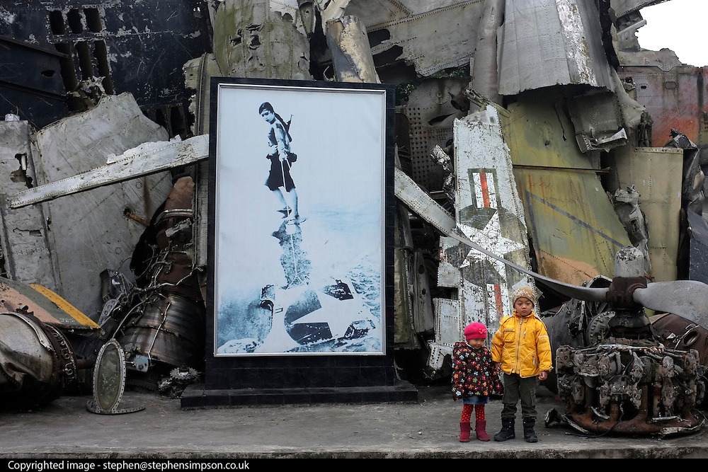 © Licensed to London News Pictures. 01/01/2012. Young children, at the Army Museum in Hanoi, pose in front of a collection of pieces from an American Aircraft which was shot down during the American War, Vietnam. Photo credit : Stephen Simpson/LNP