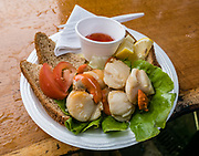 Delicious scallops, seafood lunch. Have a delicious fresh meal at Oban Seafood Hut (the Green Shack). Oban is an important tourism hub and Caledonian MacBrayne (Calmac) ferry port, protected by the island of Kerrera and Isle of Mull, in the Firth of Lorn, Scotland, United Kingdom, Europe.