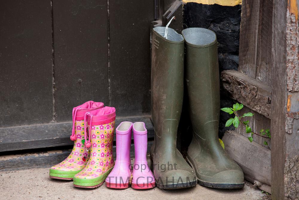 Wellington boots at front door of cottage in Bossington in Exmoor, Somerset, United Kingdom