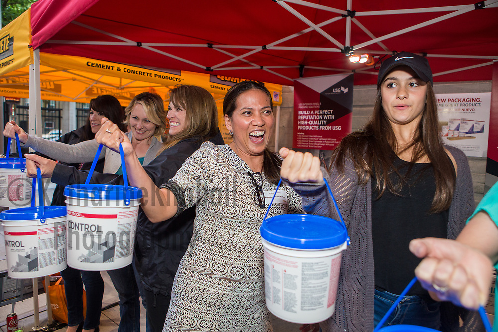 Women compete in a contest to see who can hold the heavy bucket the longest at the Home Depot event at Providence Park, Portland, Oregon,