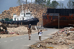 A huge coal barge destined for the cement factory at Loh Nga and its tug lie stranded on the land, dumped on the road by the force of the 26th Dec Indian Ocean tsunami, near Banda Aceh.