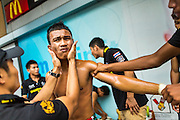 28 JULY 2013 - BANGKOK, THAILAND:  A boxer is oiled up and stretched before his bout during the ASEAN Muay Thai Championship at MBK shopping center in Bangkok.      PHOTO BY JACK KURTZ