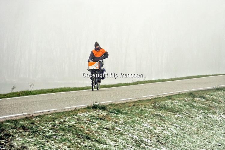 Nederland, Nijmegen, 31-1-2019 Een vrouwelijke postbezorger rijdt, fietst over de dijk. Foto: Flip Franssen