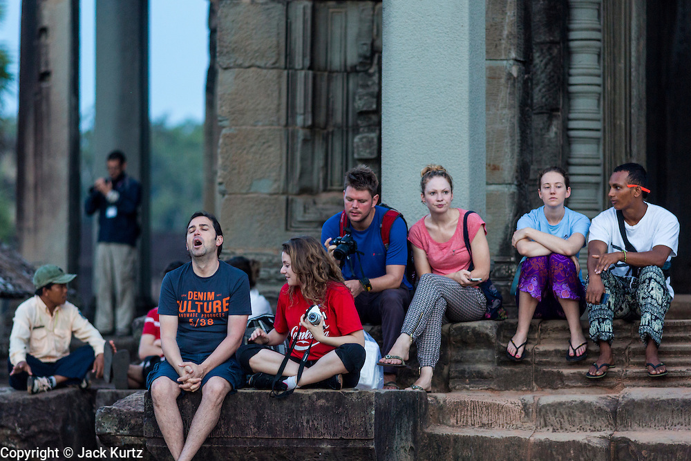 "02 JULY 2013 - ANGKOR WAT, SIEM REAP, SIEM REAP, CAMBODIA:  Tourists wait on the west side of Angkor Wat to see the sunrise from behind the temple. Angkor Wat is the largest temple complex in the world. The temple was built by the Khmer King Suryavarman II in the early 12th century in Yasodharapura (present-day Angkor), the capital of the Khmer Empire, as his state temple and eventual mausoleum. Angkor Wat was dedicated to Vishnu. It is the best-preserved temple at the site, and has remained a religious centre since its foundation – first Hindu, then Buddhist. The temple is at the top of the high classical style of Khmer architecture. It is a symbol of Cambodia, appearing on the national flag, and it is the country's prime attraction for visitors. The temple is admired for the architecture, the extensive bas-reliefs, and for the numerous devatas adorning its walls. The modern name, Angkor Wat, means ""Temple City"" or ""City of Temples"" in Khmer; Angkor, meaning ""city"" or ""capital city"", is a vernacular form of the word nokor, which comes from the Sanskrit word nagara. Wat is the Khmer word for ""temple grounds"", derived from the Pali word ""vatta."" Prior to this time the temple was known as Preah Pisnulok, after the posthumous title of its founder. It is also the name of complex of temples, which includes Bayon and Preah Khan, in the vicinity. It is by far the most visited tourist attraction in Cambodia. More than half of all tourists to Cambodia visit Angkor.         PHOTO BY JACK KURTZ"